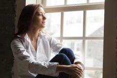 Vrouw door het venster Stock Foto