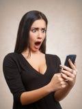 Vrouw door mobiel telefoonnieuws of bericht dat wordt geschokt Stock Afbeeldingen