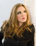 Vrouw door zonneblinden Royalty-vrije Stock Foto's
