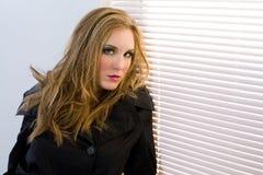 Vrouw door zonneblinden Royalty-vrije Stock Foto