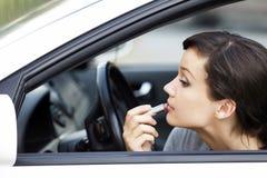Vrouw in een auto die make-up doet Stock Foto's