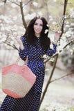 Vrouw in een blauwe kleding en een gebreide zak dichtbij magnolia het bloeien royalty-vrije stock afbeelding