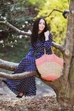 Vrouw in een blauwe kleding en een gebreide zak dichtbij magnolia het bloeien stock foto