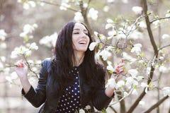 Vrouw in een blauwe kleding en een gebreide zak dichtbij magnolia het bloeien royalty-vrije stock foto's