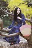 Vrouw in een blauwe kleding en een gebreide zak dichtbij magnolia het bloeien royalty-vrije stock afbeeldingen