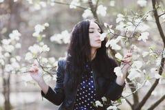 Vrouw in een blauwe kleding en een gebreide zak dichtbij magnolia het bloeien stock fotografie