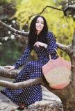 Vrouw in een blauwe kleding en een gebreide zak dichtbij magnolia het bloeien stock afbeelding