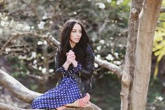 Vrouw in een blauwe kleding en een gebreide zak dichtbij magnolia het bloeien stock afbeeldingen
