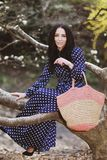 Vrouw in een blauwe kleding en een gebreide zak dichtbij magnolia het bloeien royalty-vrije stock foto