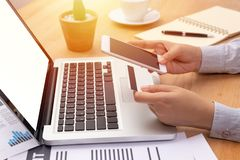 Vrouw een creditcard en een aankoop die verrichtend online betaling via mobiele smartphone met het lege scherm voor computer houd stock afbeeldingen