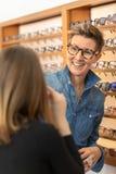 Vrouw in een eyewear opslag stock afbeeldingen