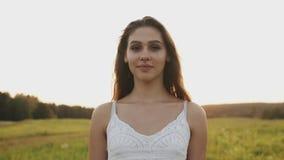 Vrouw in een goede stemming die zich op gebied op de zomeravond bevinden Zij onderzoekt camera en glimlacht stock video