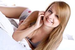 Vrouw in een grijs overhemd op het bed Stock Afbeelding
