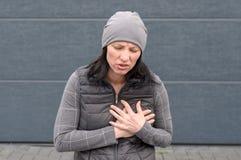 Vrouw in een grijze de winteruitrusting die haar borst clutching royalty-vrije stock afbeeldingen