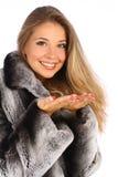 Vrouw in een grijze laag met open handenpalm Stock Foto's