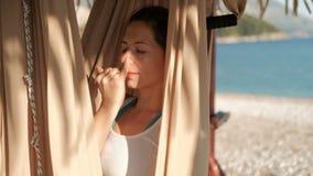 Vrouw in een hangmat op de strandyoga die afwisselende ademhaling ademen stock videobeelden