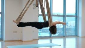 Vrouw in een hangmat voor yogaschommeling in een uitgebreid lichaam stock video