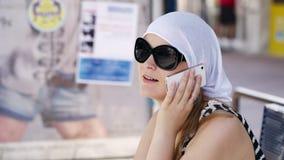 Vrouw in een headscarf die op mobiel babbelen stock video