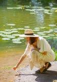Vrouw in een heldere de zomerkleding op de kust van de vijver royalty-vrije stock afbeelding