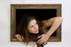 Vrouw in een het schilderen frame Stock Foto's