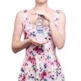 Vrouw in een kledings bloemendruk in de zomer van de het waterlente van de handenfles royalty-vrije stock fotografie