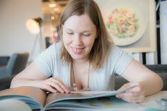 Vrouw in een koffie die aan menu kijken royalty-vrije stock foto