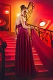 Vrouw in een lange kleding die op de treden ligt Royalty-vrije Stock Foto's