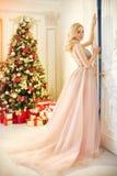 Vrouw in een lange roomkleurige kleding, die zich dichtbij de Kerstboom en de deur bevinden Het luxueuze blonde in avondjurk vier stock foto's