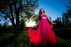 Vrouw in een lange roze kleding Stock Afbeeldingen
