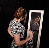 Vrouw in een overhemd die in de spiegel kijken stock afbeelding