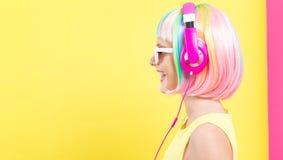 Vrouw in een pruik met hoofdtelefoons royalty-vrije stock foto