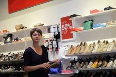 Vrouw in een schoenopslag Stock Fotografie