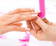 Vrouw in een schoonheidssalon die een manicure ontvangen Stock Afbeeldingen