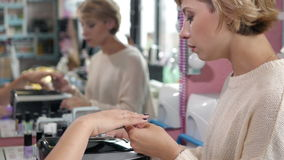 Vrouw in een spijkersalon die manicure door schoonheidsspecialist met dossier ontvangen getting spijkers aan klant vaag stock afbeeldingen