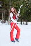 Vrouw in een sportief kostuum met skis in-gebied Stock Afbeelding