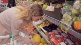 Vrouw in een supermarkt bij de plantaardige plank die voor kruidenierswinkels winkelen, controleert hij de kruidenierswinkels stock video