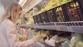 Vrouw in een supermarkt bij de plantaardige plank die voor kruidenierswinkels winkelen, controleert hij de kruidenierswinkels stock videobeelden