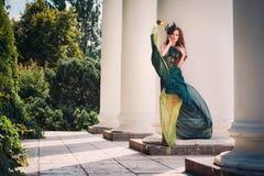 Vrouw in een vliegende kleding die zich dichtbij de kolom bevinden Royalty-vrije Stock Foto