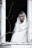 Vrouw in een wit blad dichtbij het venster Stock Foto