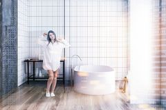 Vrouw in een witte tegelbadkamers Royalty-vrije Stock Afbeeldingen