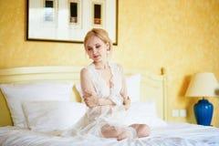 Vrouw in elegante kantrust togazitting op bed bij vroege ochtend royalty-vrije stock foto