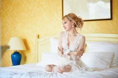 Vrouw in elegante kantrust togazitting op bed bij vroege ochtend stock afbeelding
