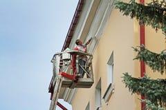 Vrouw in emmer bij hoogte het schilderen voorgevel van het inbouwen van Vitebsk stock afbeeldingen