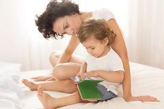 Vrouw en babymeisjeslezing op bed Stock Fotografie