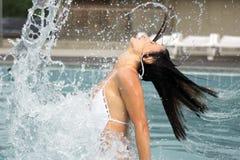 Vrouw en bogen van water in pool Stock Afbeelding