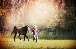 Vrouw en bruin paard die over weide met grote bomen lopen Royalty-vrije Stock Foto's