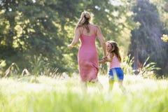 Vrouw en de jonge handen van de meisjes lopende holding Stock Afbeeldingen