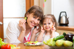 Vrouw en dochter die en pret in kitch koken hebben Stock Afbeeldingen