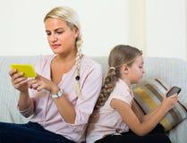 Vrouw en dochter met smartphones Stock Foto