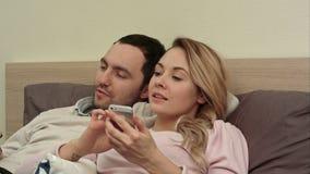 Vrouw en echtgenoot die op grappige film, het bespreken, vrouw letten gebruikend smartphone stock video